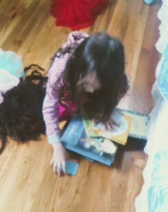 one child (children) cleaning up books off the floor