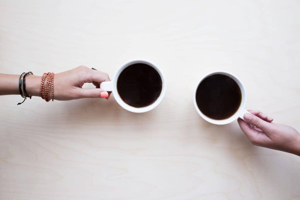 hands holding coffee -- neighbors welcome