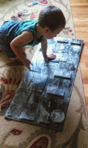 little boy looking at an advent calendar on the floor