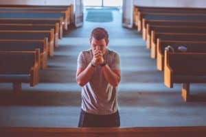man alone in a church praying