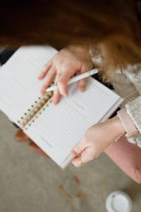 woman holding notebook and pen - creating a welcoming home