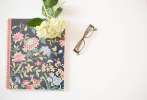 notebook with glasses and flower